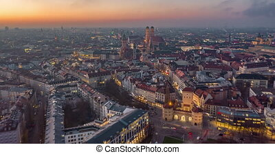 Beautiful Munich, Germany Establishing Shot Hyper Lapse above City Center with Frauenkirche Cathedral and Marienplatz, Day to Night Time Lapse with Sunset and Big City traffic 4K