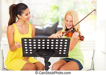 music teacher tutoring young girl to play violin