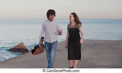 Beautiful musician couple walk walk along the pier by the...