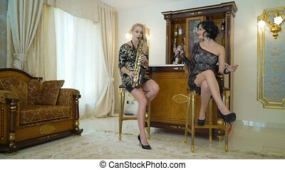 Beautiful musicians blonde and brunette young women is singing song, playing the saxophone. Sexy girls in golden black dresses perform sings plays sax at home or party, sits on chair, practice