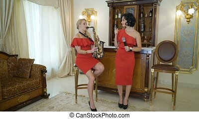 Beautiful musicians blonde and brunette young women is singing song, playing the saxophone. Sexy girls in red dresses perform sings plays sax at home or party, sits on chair, practice