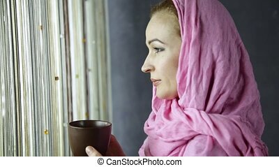 beautiful muslim arabian woman in pink hijab drinks cofee in front of window