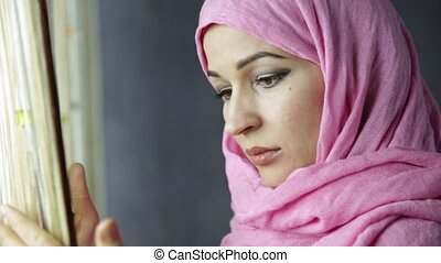 beautiful muslim arabian woman in pink hijab looking out the...