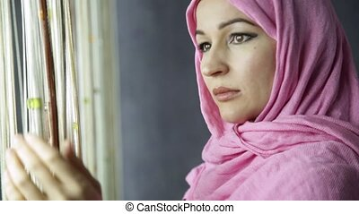 beautiful muslim arabian woman is looking at the curtains.