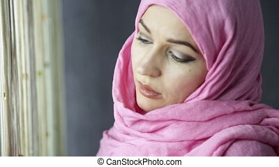 beautiful muslim arabian woman is looking at the curtains
