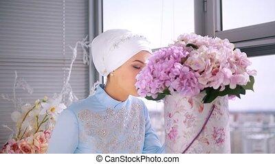 Beautiful muslim bride in beautiful wedding dress, smelling flower