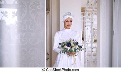 Beautiful muslim bride in wedding dress with bridal headdress in studio
