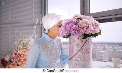 Beautiful muslim bride with make up in blue traditional dress for nikah sitting near the window