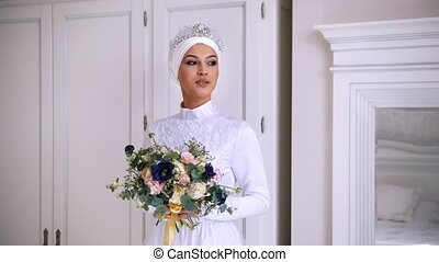 Beautiful muslim bride with make up in wedding dress with white headdress