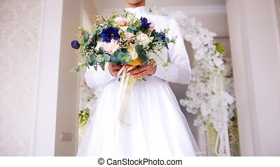 Beautiful muslim bride with make up in white wedding dress comes to the flowers