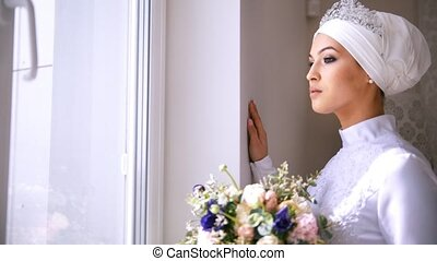 Beautiful muslim bride with make up looks out the window and...