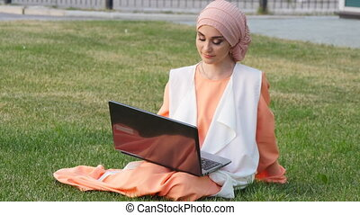 Beautiful muslim girl at park with notebook