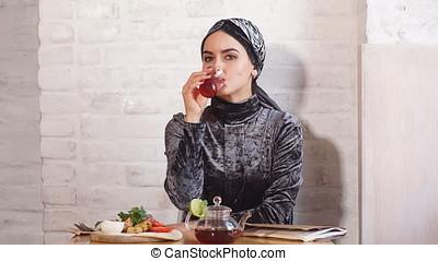 Beautiful Muslim girl in hijab drinking tea in cafe. -...