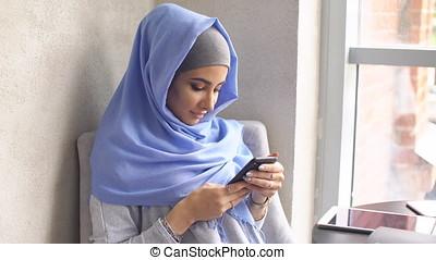 Beautiful Muslim Girl Using Smartphone in Cafe.