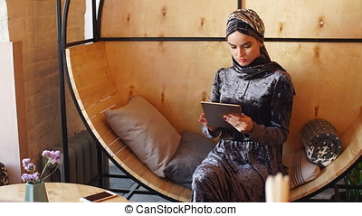Beautiful muslim girl working with tablet in cafe.