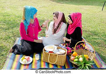 Beautiful Muslim girlfriends on picnic at sunny day