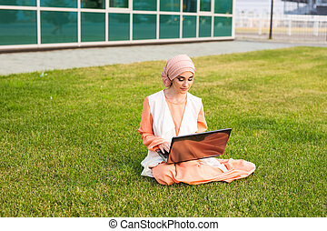 beautiful muslim woman at park with notebook