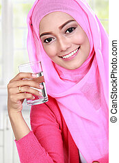 beautiful muslim woman holding a glass