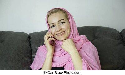 beautiful muslim woman in pink hijab sitting on a sofa in a...