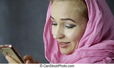 beautiful muslim woman in pink hijab talking on cell phone