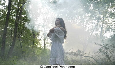 Beautiful mysterious woman dancing in the fog in the forest