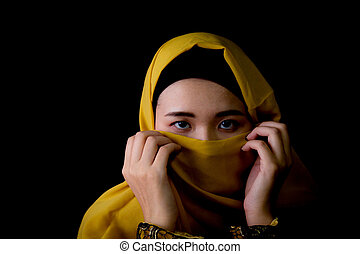 beautiful mysterious young woman wearing scarf close up.