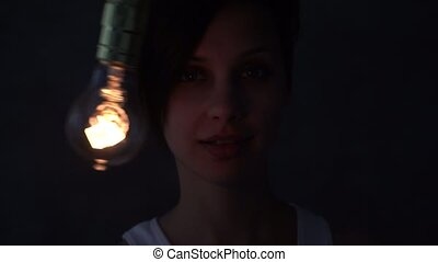 Beautiful mystical girl with a light bulb in front of her...