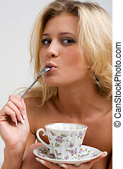 naked blonde is drinking tea in the bed