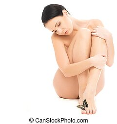 Beautiful naked brunette woman with butterfly on her leg isolated on white background