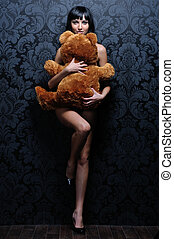 Beautiful naked girl is holding the teddy bear