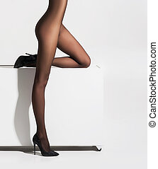 Beautiful naked legs in pantyhose over white background