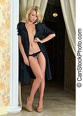 Beautiful naked woman in black silk robe in luxury interior.