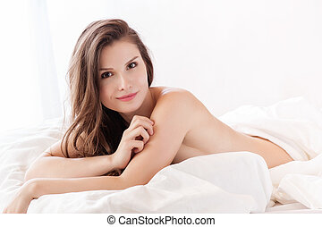 beautiful naked woman lying in bed and covering herself with white sheet