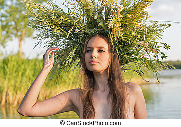 Beautiful naked young woman with wreath have fun in water.