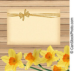 beautiful narcissus flowers and card on wooden table background
