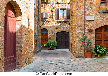 Beautiful narrow alley with traditional historic houses at Pienza city