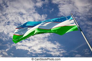 Beautiful national state flag of Uzbekistan fluttering at sky background. Low angle close-up Uzbekistan flag 3D artwork.