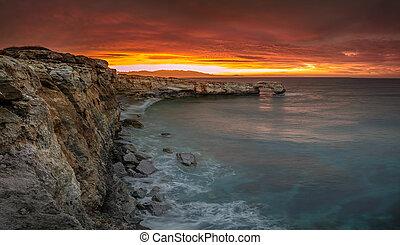Beautiful natural big rock arch at sunset near Rethimno, Crete.