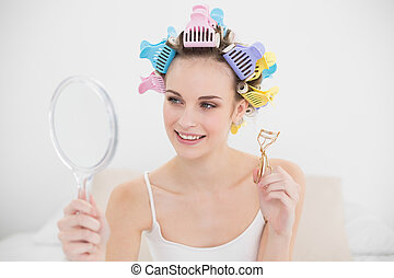 Beautiful natural brown haired woman in hair curlers looking herself in a mirror in bright bedroom