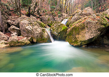 beautiful nature - flowing water between stones in the mountains, boulders covered with moss