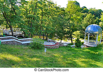 Beautiful nature in the park on a clear sunny afternoon. With a green slope and a descending downhill leading to the gazebo with a domed roof.