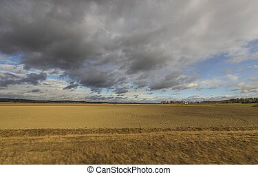Beautiful nature landscape view on a spring day. Plowed field merging with blue sky and rain clouds.