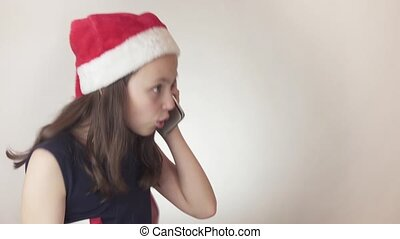 Beautiful naughty girl teenager in a Santa Claus hat...