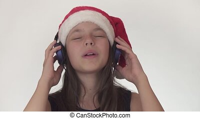 Beautiful naughty girl teenager in a Santa Claus hat listens...