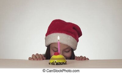 Beautiful naughty girl teenager in Santa Claus hat secretly blows out candle on festive cake and happily hides on white background