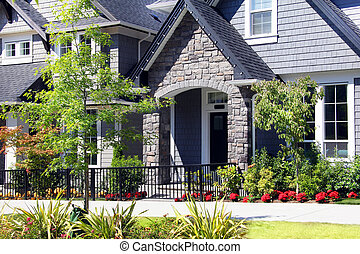 Beautiful new contempory suburban houses with colorful summer gardens in a Canadian neighborhood.