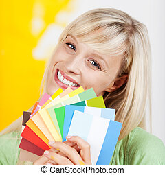 Gorgeous blonde woman holding up a selection of beautiful new paint colours on swatches when renovating and decorating her house