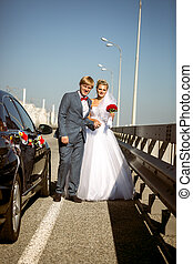 newly married couple walking on highway at sunny day