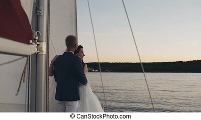 Beautiful newlyweds couple hug, stand on board of sailboat. Bride and groom in wedding outfit looking at distance.