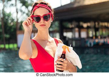 Beautiful nice young woman fixing her sunglasses